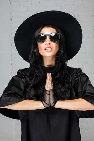 escalation: Model in studio close-up with long black hair posing to the photograther like she is praying
