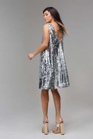 Posing model standing with his back to the photographer in a grey dress