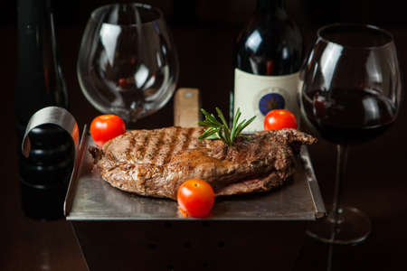 Tasty grilled steak with tomato and vine on the pan on a wooden table Stock Photo