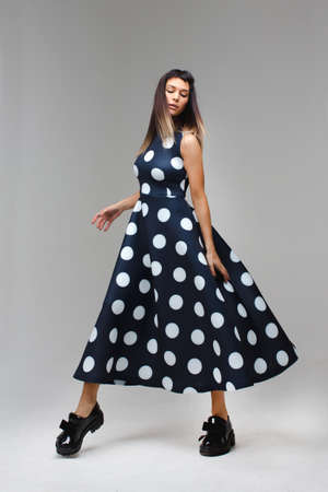 Model in a long polka dot dress which walks with closed eyes and her dress flies Stok Fotoğraf