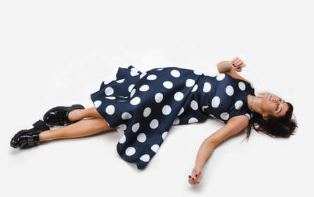 Woman which relaxed sprawled on the floor and looking up in polka dot dress
