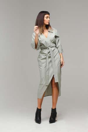 Woman standing in grey coat and looking sideways