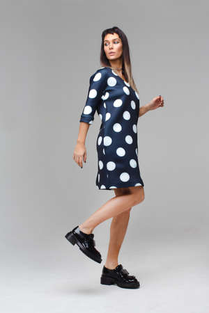 role model: Model in blue dress with polka dots making steps
