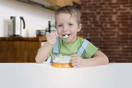 Five years boy eats porridge on the kitchen
