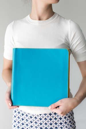Female holding blue paper folder Stock Photo