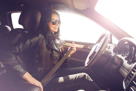fastens: Brunette in sunglasses woman fastens expensive car