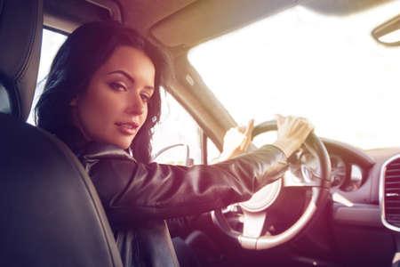 steers: Beautiful brunette woman steers car expensive car