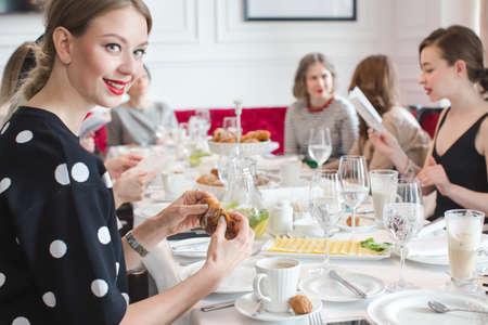 Elegant women sitting at table having dinner in luxurious restaurant. Girl breaks the croissant 版權商用圖片