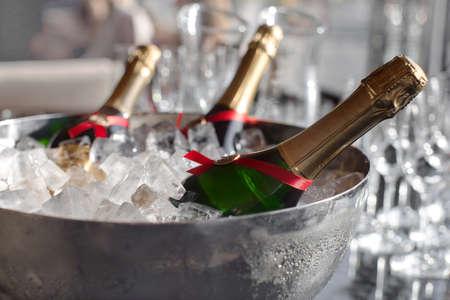 Three wine bottles chill in ice bucket