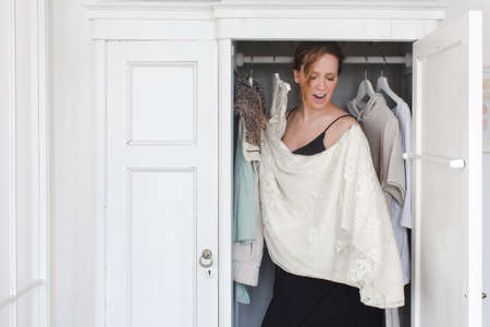messy clothes: A woman is overwhelmed in closet of messy clothes