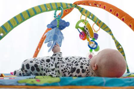 Feliz bebé sonriente en el tapete de juego