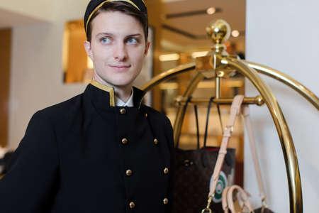 Young man in uniform serving in hotel Stock fotó