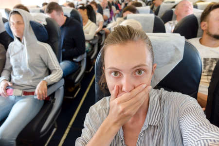 Scared woman in airplane Stockfoto