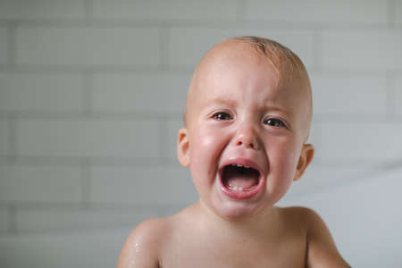 One-year-old baby cries close-up six teeth visible Stock Photo