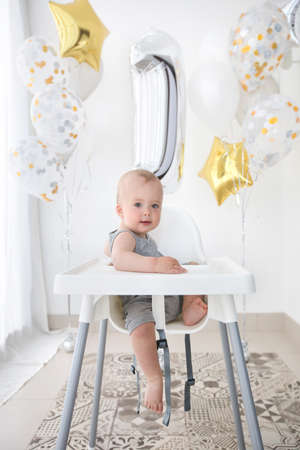 Adorable child in high chair celebrating birthday