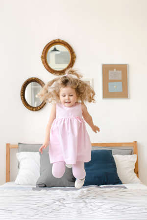 Cute little girl jumping on white bed in a pink dress Stok Fotoğraf