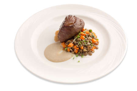 Image of a steak fillet on a bed of lentil and sauce on plate isolate