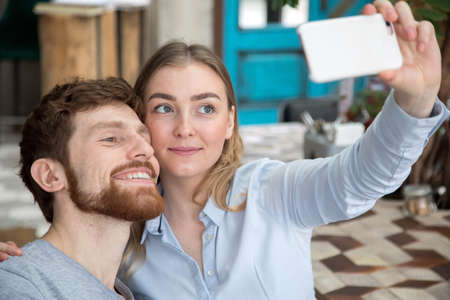 Content man and woman posing for selfie using smarpthone.