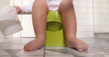 Funny baby boy sitting on chamberpot, Childrens legs hanging down from a chamber-pot. Kid plays toilet paper Stock Photo