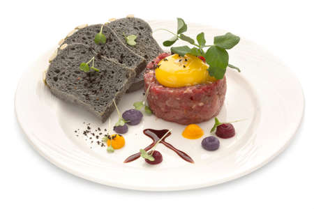 Tartar with black bread and yolk. Molecular modern cuisine. Chips Pigskin with tartare or carpaccio of beef. Stock image. Isolated on white. Stock Photo