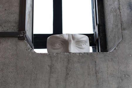 窓の端に立つ顔の石膏断片 写真素材