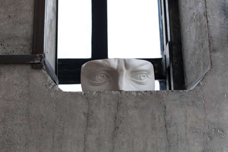 Gypsum fragment of the face that stands on the edge of the window