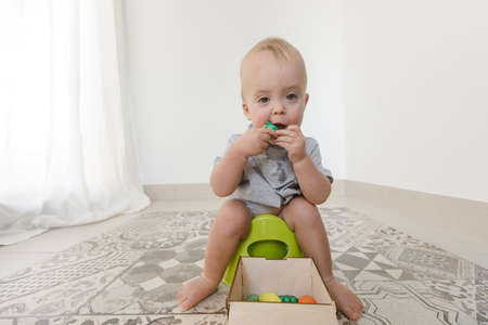Baby sitting on potty and eating vegetables at home interior Stock Photo