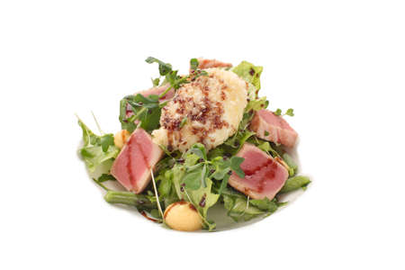 Exquisite salad of tuna, greens and green beans with balsamic vinegar on an isolated background