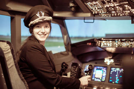 Beautiful woman pilot wearing uniform with epaulets, hat with golden wings sitting inside airliner. Girl looking at camera Stock Photo