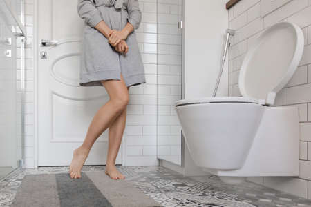 Woman with prostate problem in front of toilet bowl. Lady with hands holding People wants to pee - urinary incontinence concept Foto de archivo