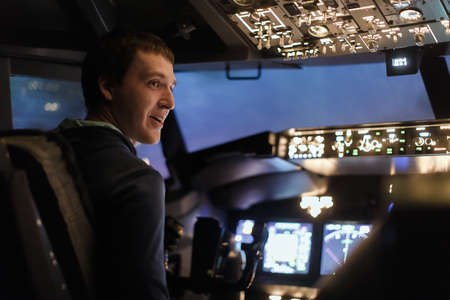 Young man piloting a plane in flight simulator for the training of the pilots