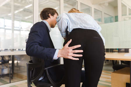 Back view of man molesting young girl at work putting hand on her bottom while working at table Standard-Bild