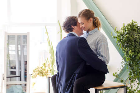 Young man and woman in formal clothes about to have sex in office on table desk among green plants