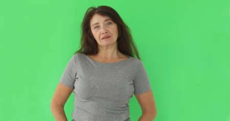 Serious wise woman looking at camera on green chromakey backdrop. Close view of somber elderly woman isolated on green screen