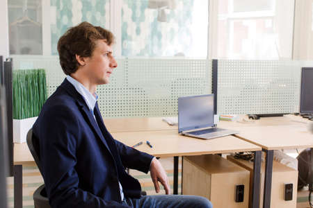 Side view of serious young employee sitting in office near table with laptop