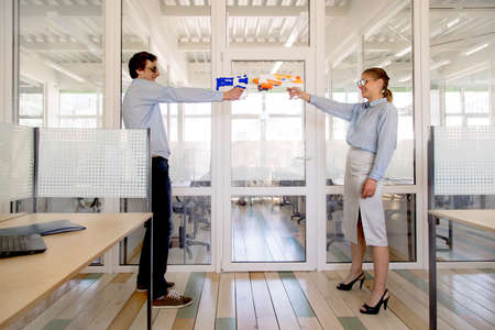 Side view of young man and woman in formal outfits and sunglasses standing opposite each other and aiming toy guns while having fun in office