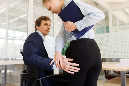 Young formal businessman sitting at table in office and touching hips of woman in sexual harassment