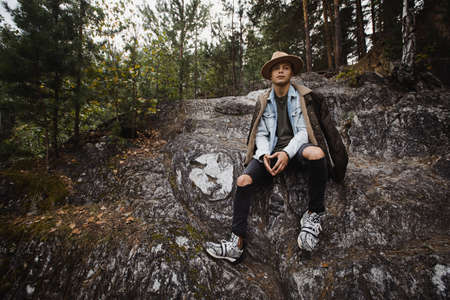 Young handsome man in jeans and warm jacket sitting on rocky cliff in forest on background of green trees Stock fotó