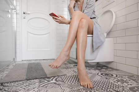 Frau sitzt auf der Toilette mit Telefon und surft im Internet