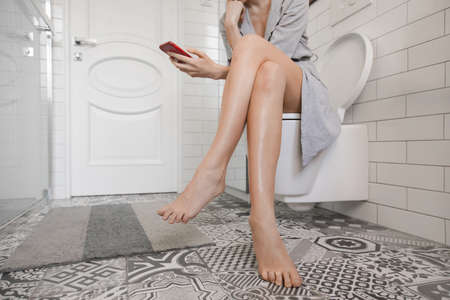 Woman sitting on the toilet with phone and surfing internet