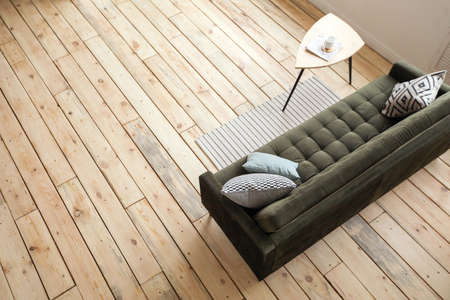 From above shot of comfortable couch and small table standing on wooden floor in spacious living room