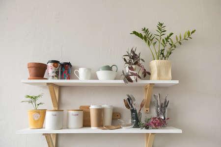 Bonitos estantes con vajillas y vasijas de cerámica colgadas en una pared blanca en una habitación elegante Foto de archivo