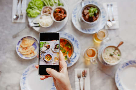 Hand of anonymous female using smartphone to take photos of delicious dishes on table