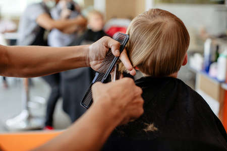 Crop hairstylist cutting hair of adorable little boy with scissors Banco de Imagens
