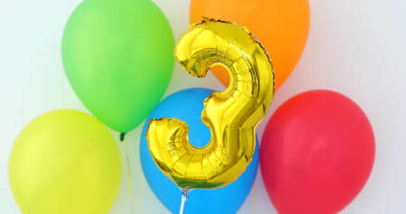 Gold foil number 3 celebration balloon on a color background