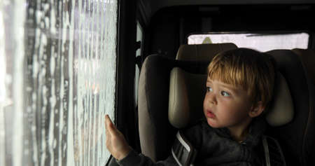 Little boy looking through misted window. Cleaning Car Using High Pressure Water. Car wash, car wash foam water. From inside the car. Foto de archivo