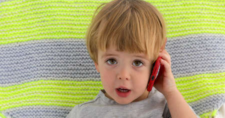 Little child boy speaks smartphone color background 스톡 콘텐츠