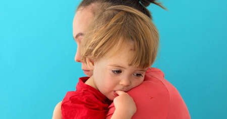 Side view of young mom cuddling sad kid with finger in mouth looking down isolated on blue background