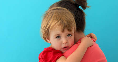 Side view of young mom cuddling sad kid looking at camera isolated on blue background Stok Fotoğraf