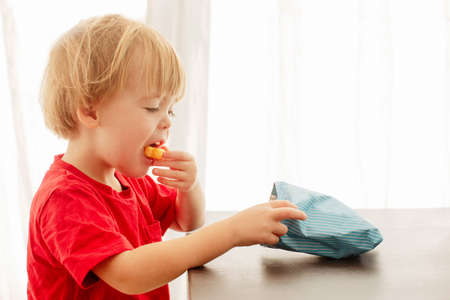 Side view of blonde child in red t-shirt with pleasure eating corn sticks holding and looking in pack on table at home Stok Fotoğraf